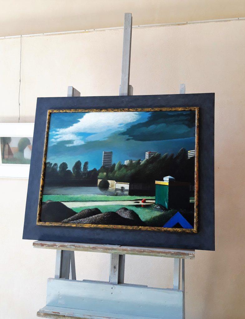 Een foto van het atelier van Hilmar Schafer, met een schildersezel waar een schilderij op staat.